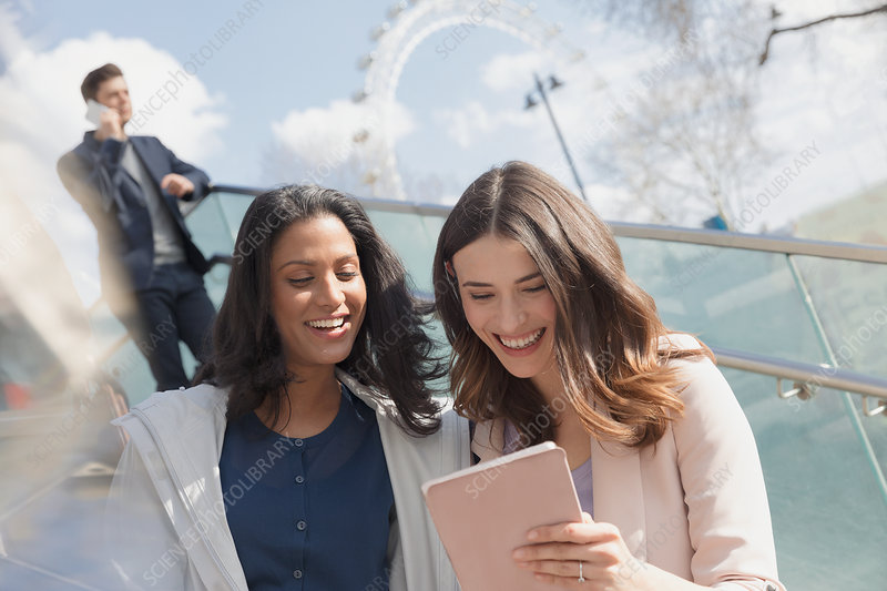 Smiling businesswomen using tablet outdoors