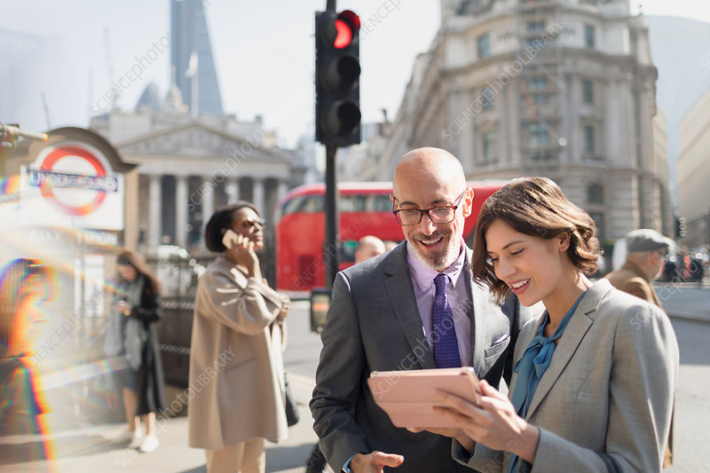 Business people using tablet, London, UK
