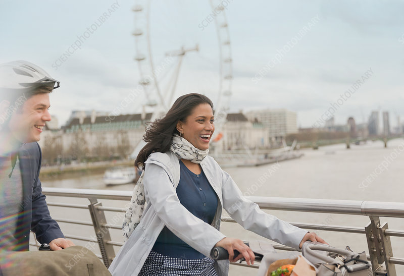 Couple bike riding on bridge, London, UK