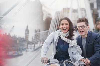 Couple bike riding on urban road, London, UK