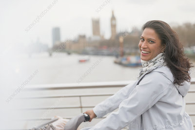 Woman bike riding on bridge, London, UK