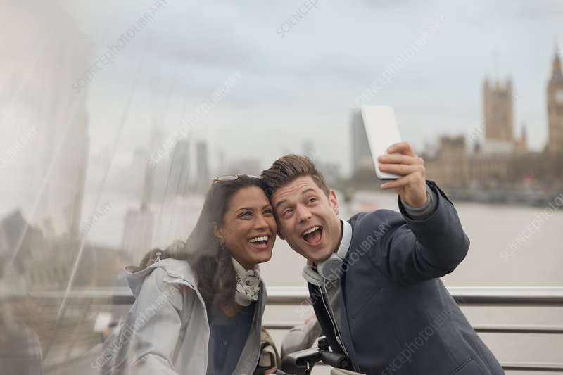 Playful couple tourists taking selfie, London, UK