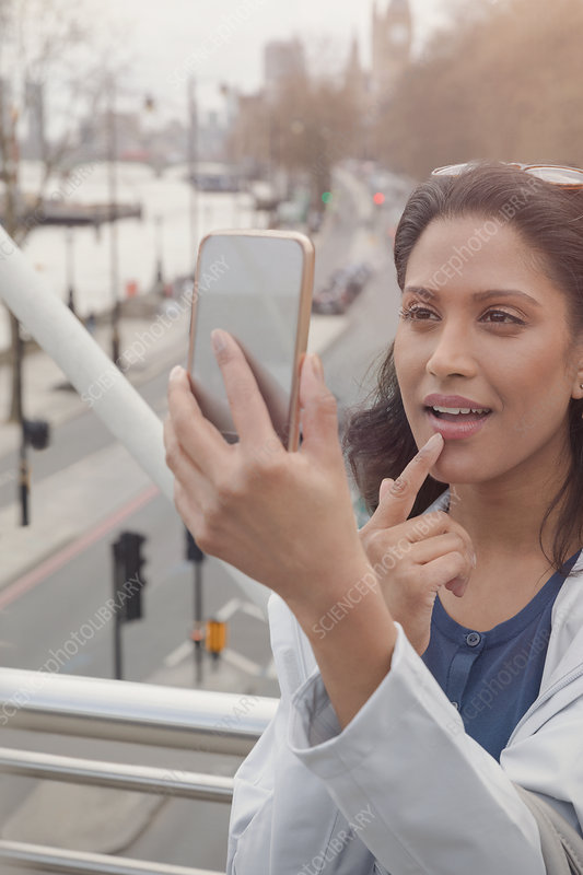 Woman checking makeup with camera phone, London