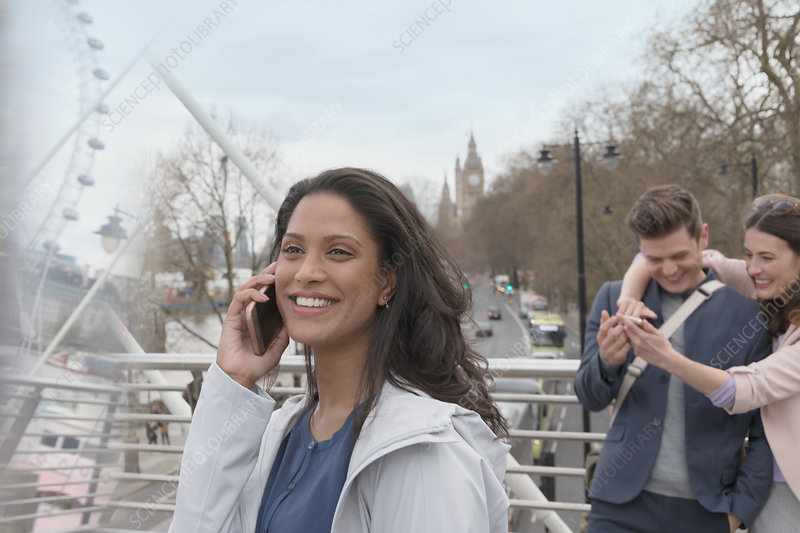 Smiling woman talking on cell phone, London, UK
