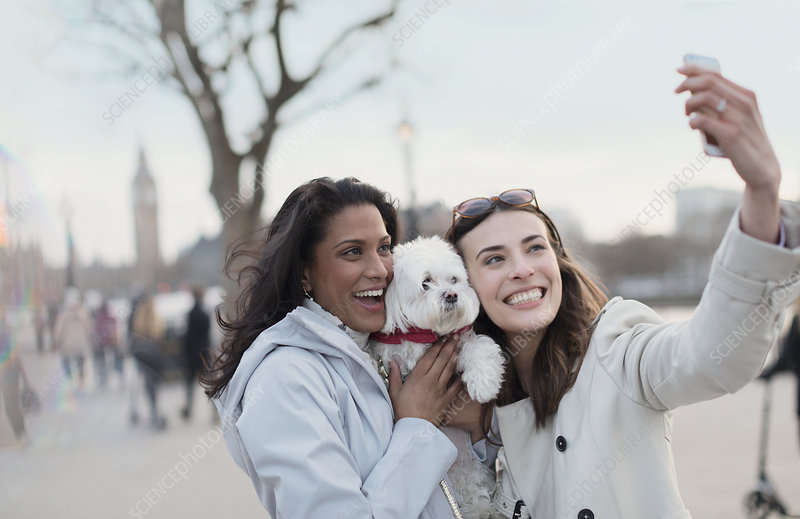 Lesbian couple with dog in urban park, London, UK