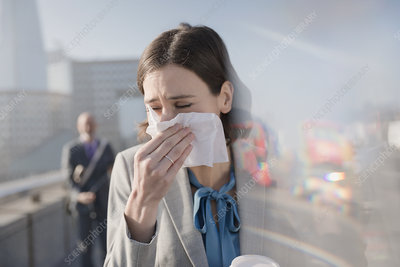 Businesswoman blowing nose into tissue