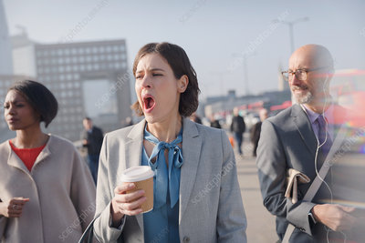 Tired businesswoman with coffee yawning
