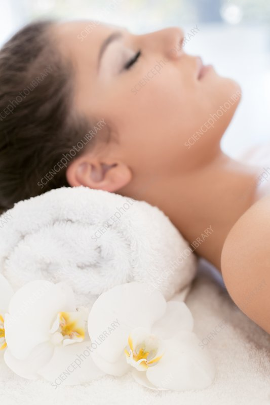 Woman lying on towel in spa