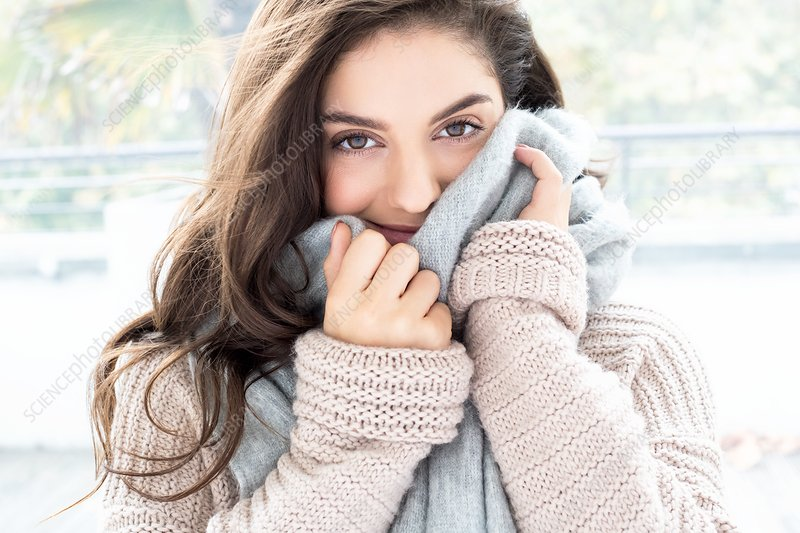 Woman wearing knitted sweater and scarf