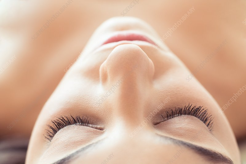 Woman lying on back with eyes closed
