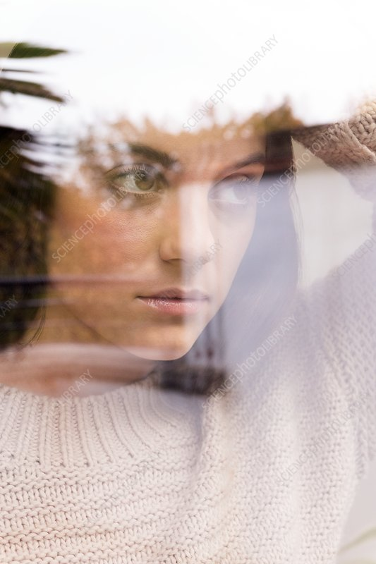Woman looking away, view through reflective glass