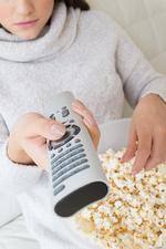Woman with tv remote eating popcorn