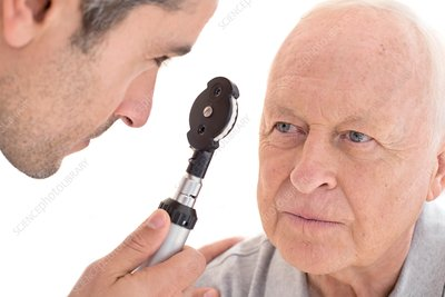Male doctor examining senior patient's eye