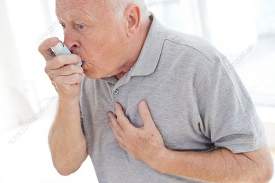 Senior man using inhaler, holding chest