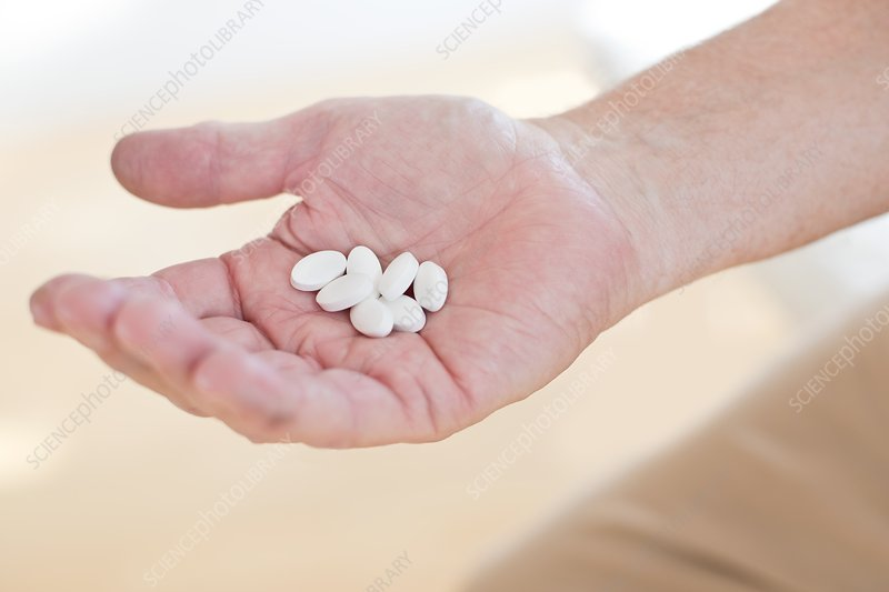 Man holding white tablets