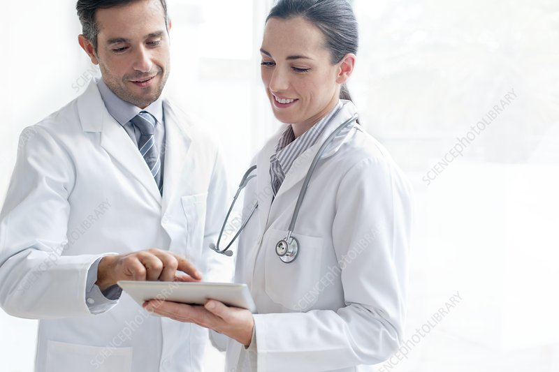 Male and female doctors using tablet