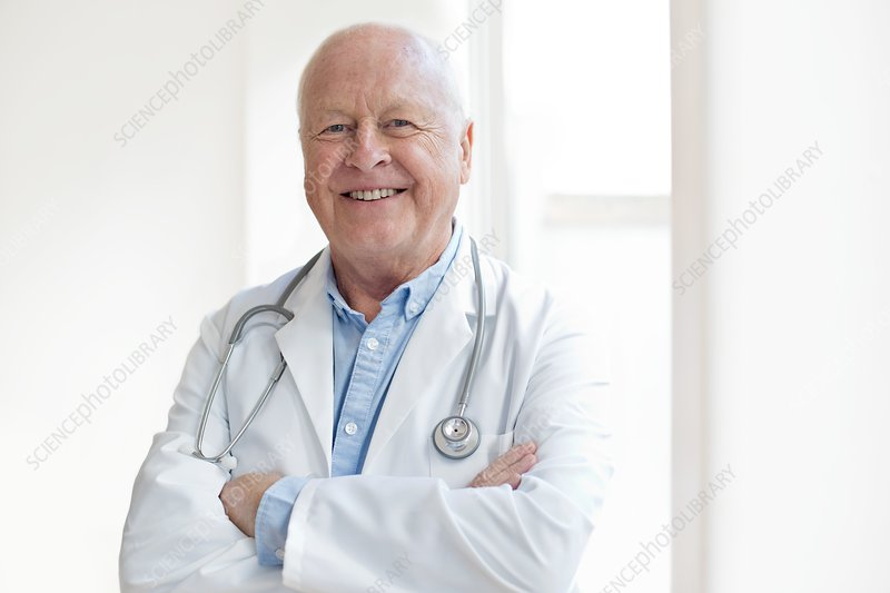 Senior male doctor smiling towards camera