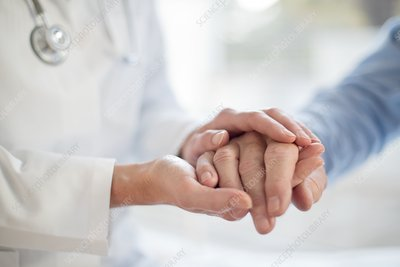 Female doctor holding patient's hand