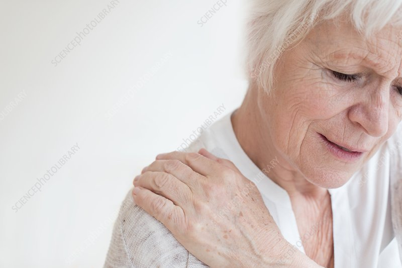 Senior woman rubbing sore shoulder