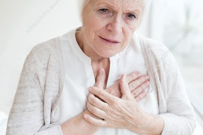 Senior woman holding chest