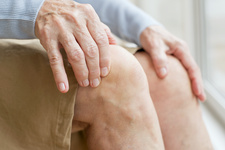 Senior woman touching knees