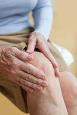 Senior woman holding sore knee