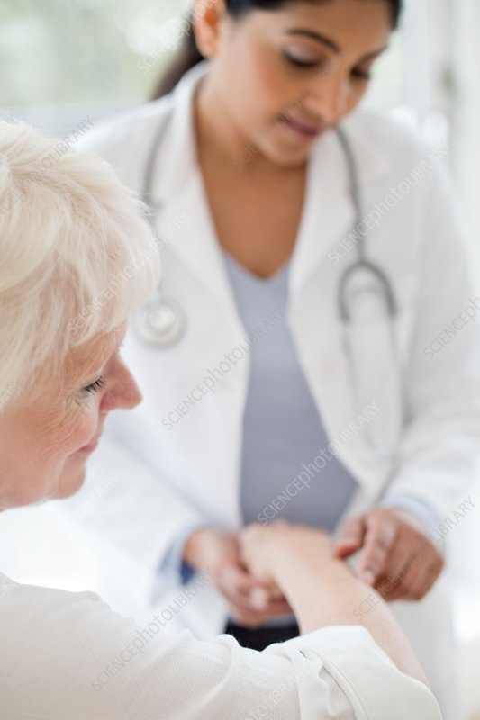 Female doctor examining patient's arm