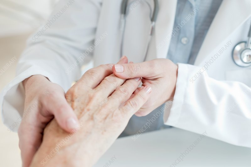 Female doctor holding senior patient's hand