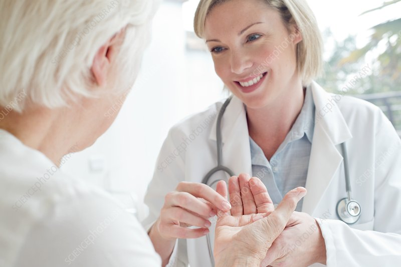 Female doctor examining senior patient's hand