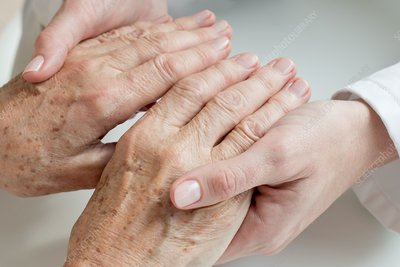 Female doctor examining senior patient's hands