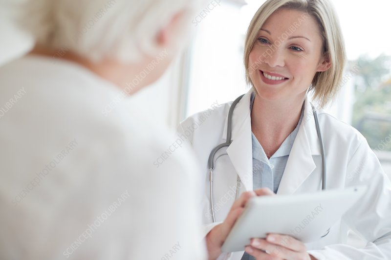 Female doctor using digital tablet with patient