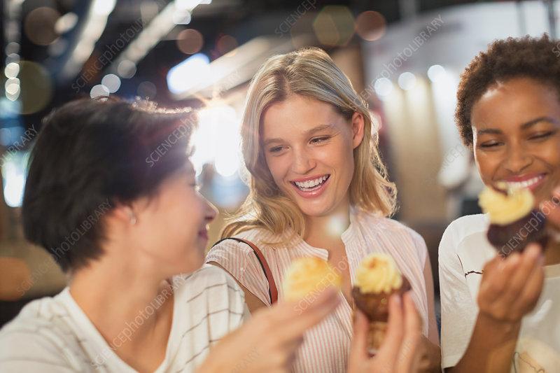 Young women eating cupcakes