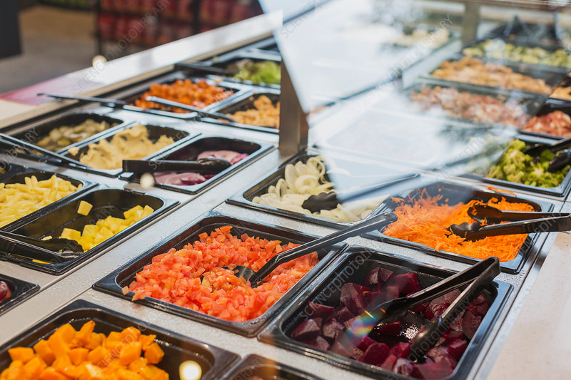 Salad bar items and tongs in market