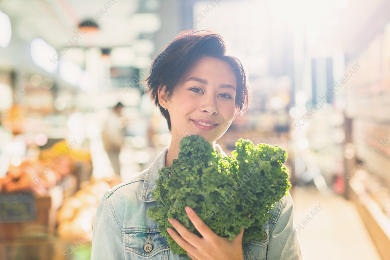 Portrait woman holding fresh kale in market