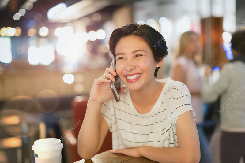 Smiling woman talking on cell phone in cafe