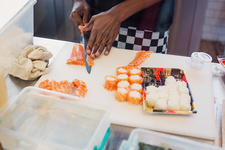 Young female chef making sushi in restaurant
