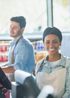 Portrait female cashier working at market checkout