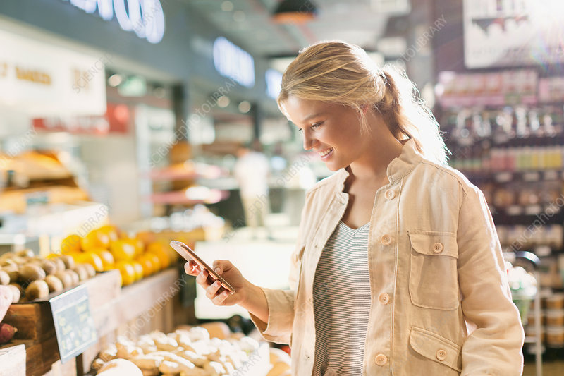Young woman using cell phone in market