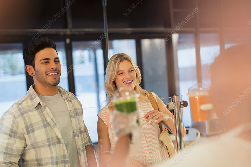 Smiling couple receiving green smoothie