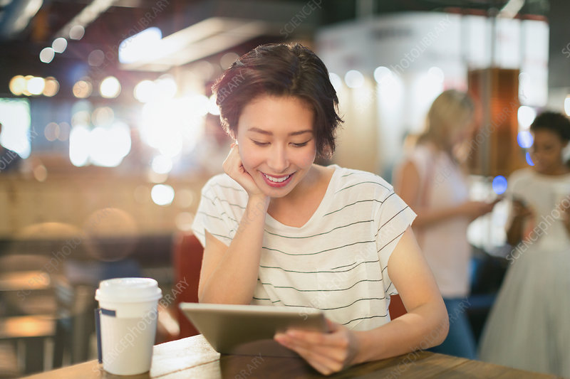 Young woman using tablet in cafe
