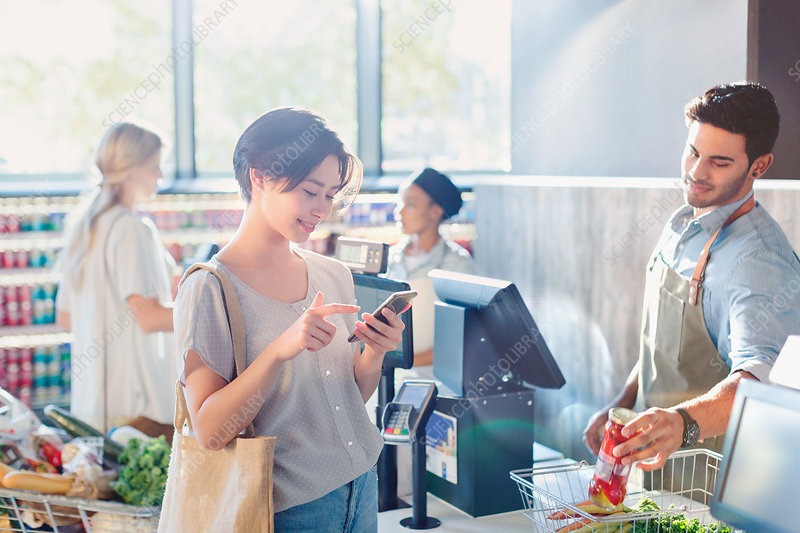 Young woman using cell phone at market checkout