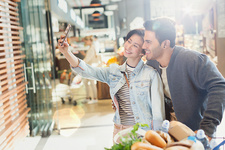 Young couple taking selfie in market