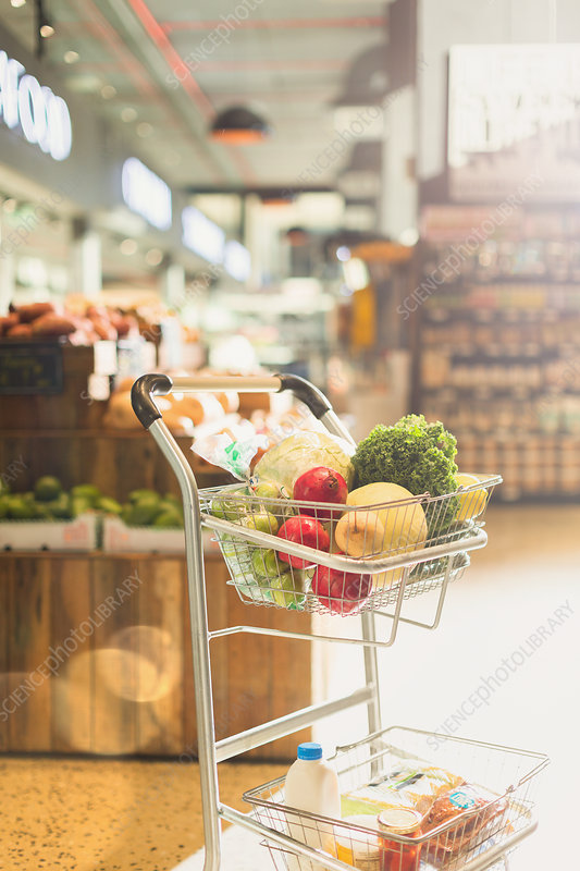 Produce and groceries in shopping cart in market