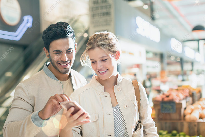 Smiling couple using cell phone in market
