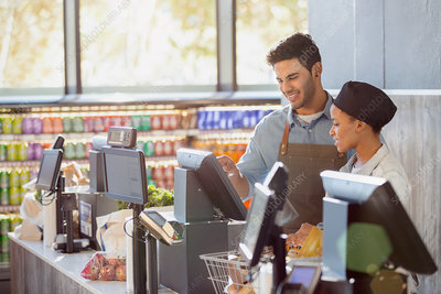 Cashiers working at grocery store checkout