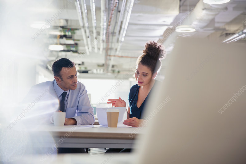 Businessman and businesswoman discussing paperwork