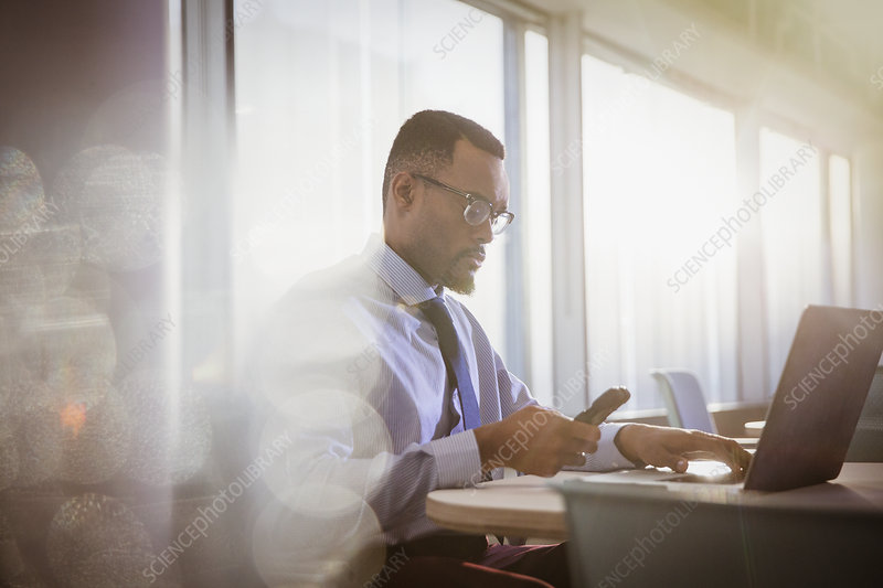 Serious businessman texting at laptop in office
