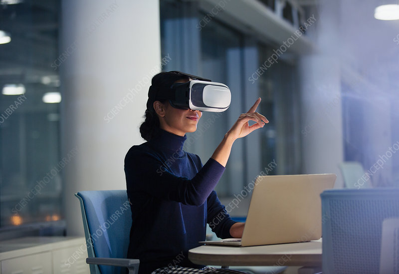 Businesswoman using VR simulator at laptop