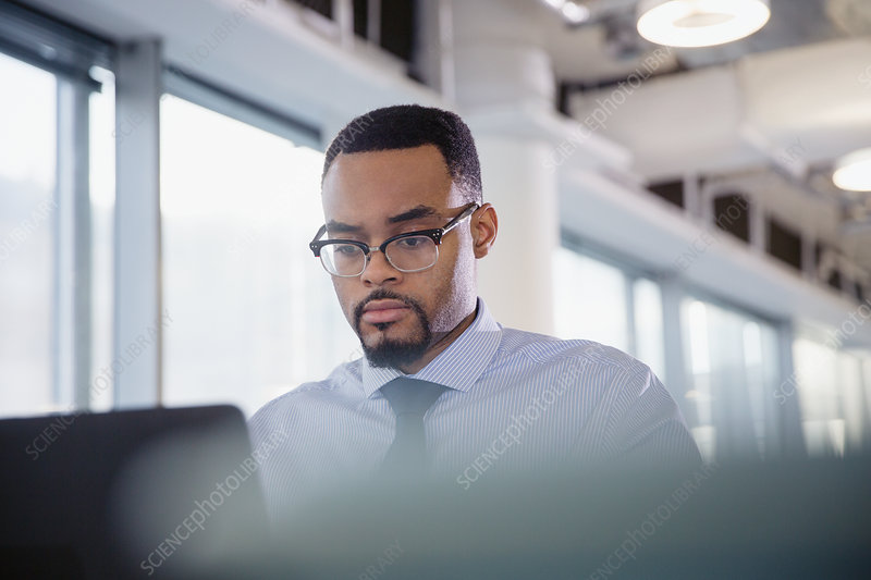 Serious, focused businessman working at laptop