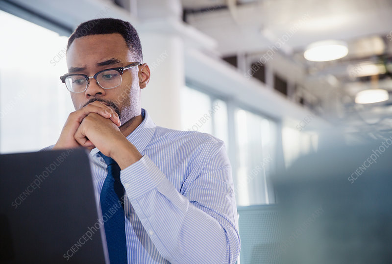 Serious, worried businessman working at laptop